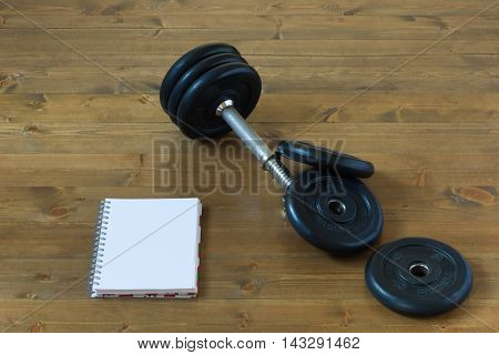 Collapsible dumbbells on a table with a sheet of paper