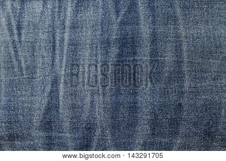 The textured background from rough cotton material, Jeans or denim of pale blue color.