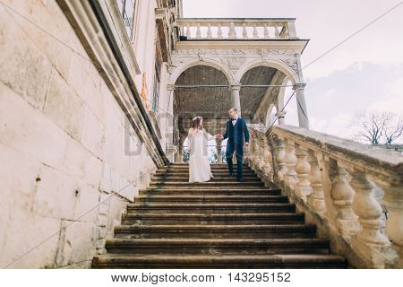 Gentle groom holding hand of his pretty bride when descending by antique palace stone stairs. Low angle shot.
