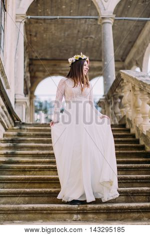Charming bride in long white wedding dress and floral wreath going down by antique stone stairs.