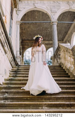 Charming bride in long white wedding dress and floral wreath going down by antique palace stone stairs.