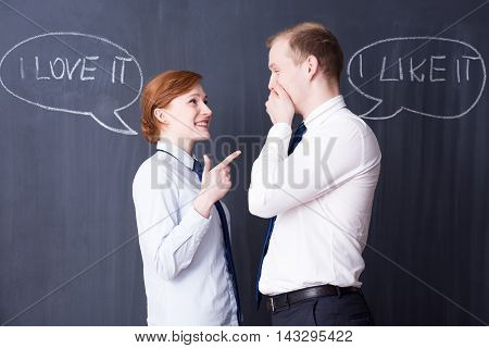 Young smartly dressed office workers laughing in front of a blackboard with chalk phrases on it