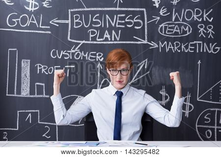 Portrait of a young confident manager sitting by the desk and pointing at a blackboard filled with charts behind her