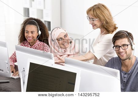 Students of different nationalities sitting in front of computers during IT course with mature teacher