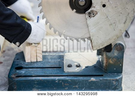 Carpenter cutting wood with electric saw in factory