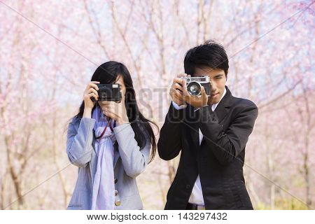 Man and girl photographer outdoors holding vintage camera.