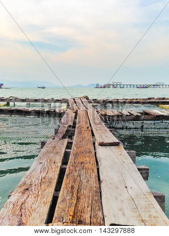 A wooden fishing bridge floating on the sea in Phuket , Thailand, with partly cloud sky and pier as a background.