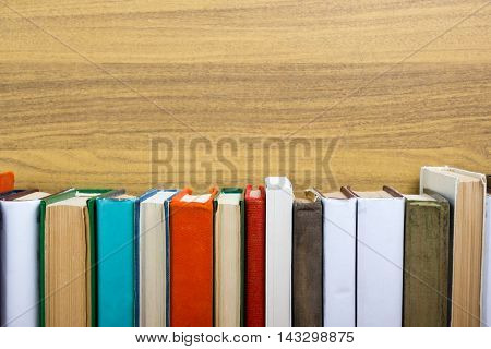 Colorful composition with vintage old hardback books, diary on wooden deck table and wood background. Books stacking. Back to school. Copy Space. Education background