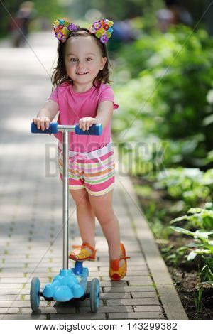 Little cute girl poses near scooter in summer sunny green park