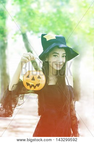 portrait of Asian woman on black dress and holding plastic pumpkin doll in garden filter in gradient vintage tone