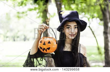 portrait of Asian woman on black dress and holding plastic pumpkin doll in garden