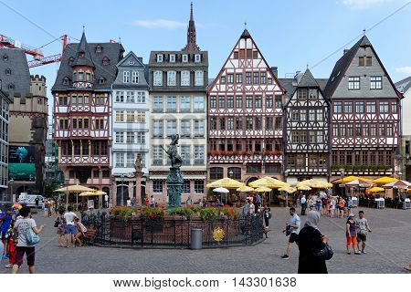 FRANKFURT AM MAIN GERMANY - AUGUST 7 2015: A row of half-timbered houses at the east side of the Romerberg square known as the Ostzeil. The Fountain of Justice in the middle.