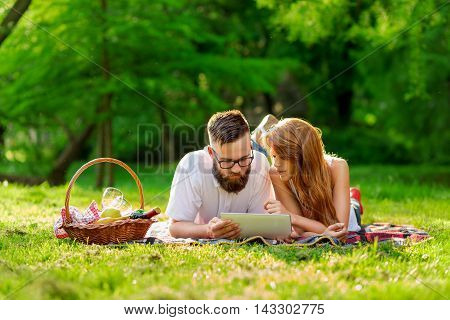 Couple lying on a picnic blanket in a park with a picnic basket filled with fruit food and wine placed next to them surfing the net on a tablet computer