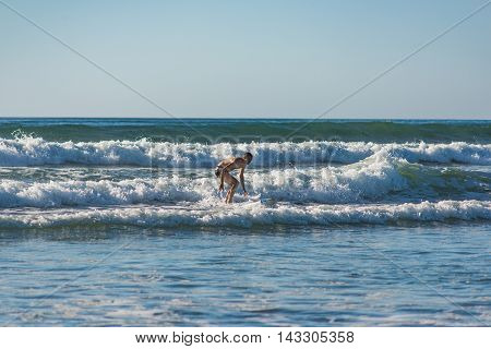 Student beginner novice male surfer trying to stay steady and ride small wave to shore in California ocean