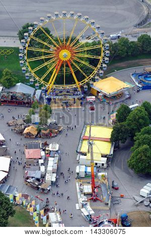 MUNICH GERMANY - 4 AUGUST 2015: Ferris Wheel in a fun fair on the grounds of the Olimpiapark near Olympia Tower.