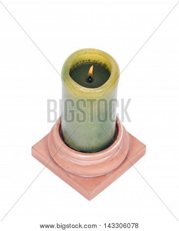 Burning green candle in clay holder separated on white background