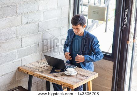 Asian Businessman Relaxing Indoor Working On Laptop With A Mug Of Latte Coffee