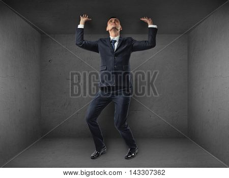 Businessman striving to escape from a small confined room by pushing upwards against the ceiling with bent knees in a conceptual image of a visionary or man thinking outside the box
