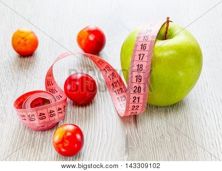 Green apple with a meter and plum on a wooden background