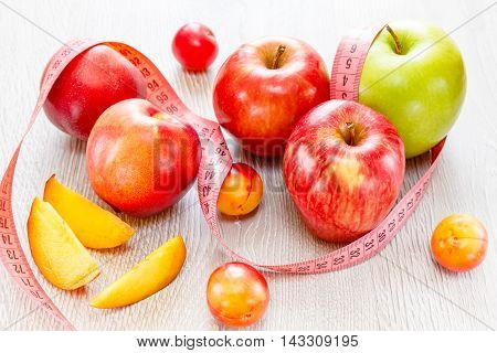 Apples nectarines plums meter tape on a wooden background