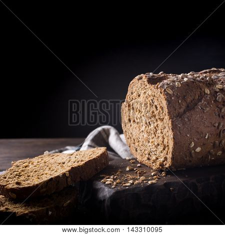 Homemade multigrain bread on wooden cutting board. Dark rustic photo with copy space.