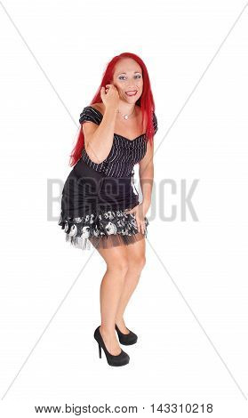 A very happy woman with long red hair and wearing a black dress isolated for white background.