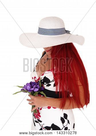 A beautiful woman in a dress holding purple flowers wearing a white hat with head down isolated for white background.