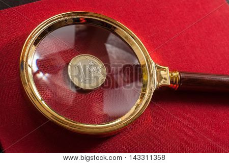 Magnifying glass on red background with a coin of euro