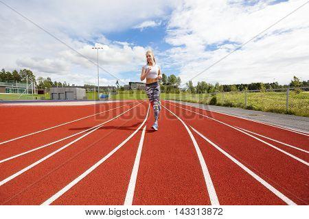 Female athlete runner or sprinter on running track. Workout outdoor.