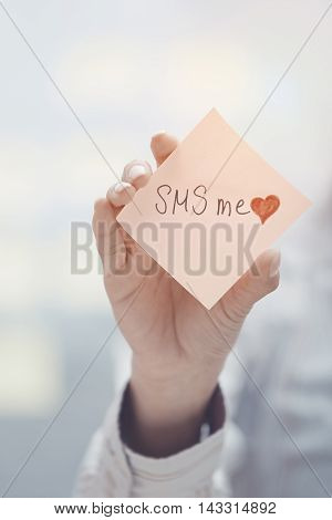 Woman holding sticky note with SMS me text