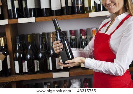 Smiling Saleswoman Holding Wine Bottle In Supermarket