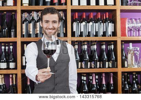 Bartender Offering Red Wine Glass Against Shelves