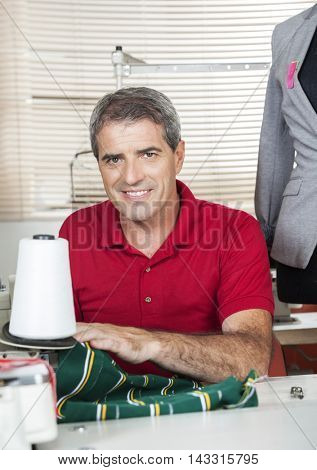 Confident Fashion Designer Working At Workbench