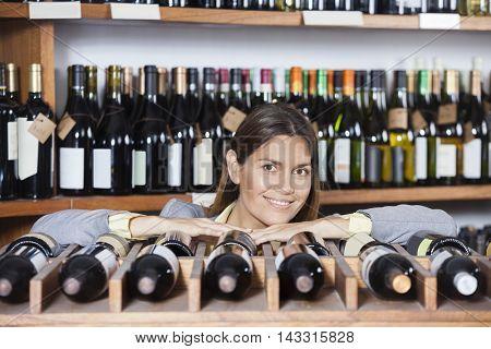 Confident Female Customer Leaning On Wine Rack