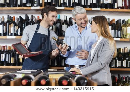 Man Holding Wine Bottle While Standing With Woman And Salesman