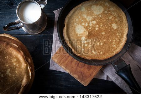 Breakfast in the rustic style: freshly cooked crepes or pancakes, one of them in a frying pan, close - milk in a metal jug. On the wooden background, top view