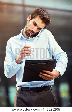 Portrait of handsome boss drinking coffee outdoor