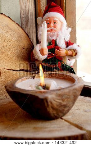 Santa Claus and a candle in a decorative coconut