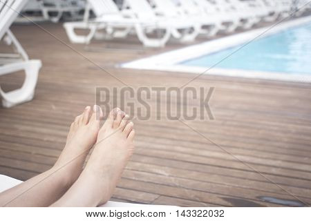 Sunbathing By Swimming Pool