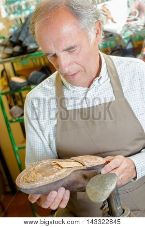 Cobbler holding shoe with no sole