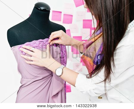 Fashion Designer Putting Lace On Dress On Dressmaker Model