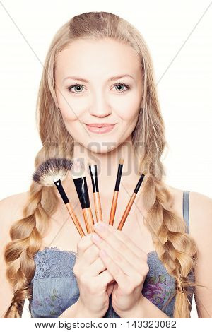 Make-up. Beautiful woman with makeup brushes on white