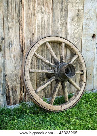 Old wooden wagon wheel resting against rustic wooden fence