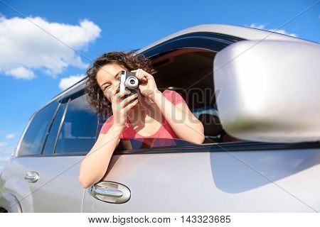 So beautiful landscape. Cropped photo of girl holding camera in her hands and taking picture of car window during trip