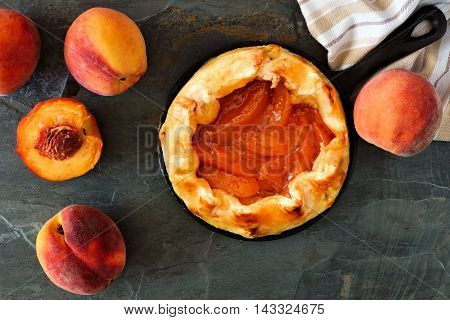 Delicious Peach Tart In Cast Iron Baking Skillet, Scene From Above Over Slate Background