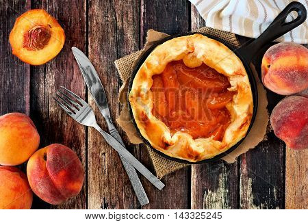Fresh Peach Tart In Cast Iron Baking Skillet, Scene From Above On Rustic Wood