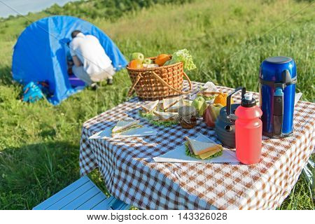 Food for entire family. Shot of outdoor lunch on table with tent in background