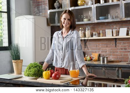 I eat only healthy food. Happy young woman is standing on kitchen and smiling