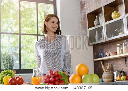 Joyful young girl is standing on kitchen near fruits and vegetables. She is looking forward with happiness and smiling