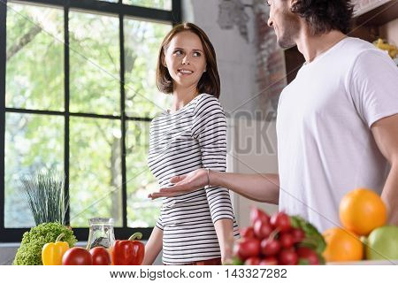 Young man is explaining to his wife how to cook. He is standing in kitchen and gesturing with aspiration. Woman is looking at husband and smiling